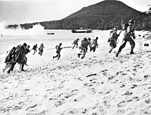 Soldiers running up a beach from the ocean