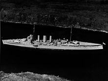 Aerial photograph of a cruiser-size warship sailing slowly through a narrow body of water