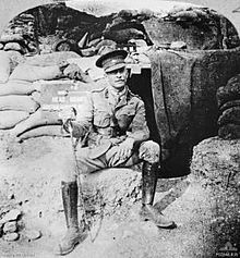 "Soldier wearing Sam Browne belt and peaked cap, with a walking stick, sitting in front of a sandbagged doorway half covered by a tarpaulin. A sign says: ""headquarters""."