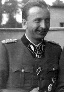A black-and-white photograph of a smiling man in semi profile wearing a military uniform and a neck order in shape of an Iron Cross.