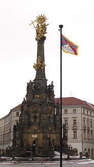 Holy Trinity Column in Olomouc with Tibetian flag.jpg