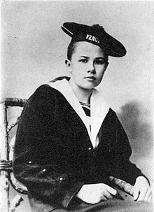 An androgynous photograph of Eberhardt as a teenager, sporting a short haircut and wearing a sailor's uniform.