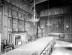 Black and white photograph of the Jerusalem Chamber. A long table is in the center. A chandelier hangs from the ceiling. There is a fireplace on one wall and a tapestry on another.