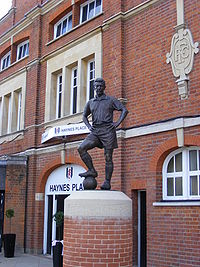 "A metal structure composed of a man made of bronze with hands on his hips. One foot is balanced on top of a bronze football. The statue is on an upright brick structure. The word ""Haynes"" is visible on a sign behind the statue."