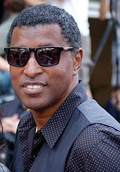 Image of Babyface wearing polka-dot shirt, sunglasses and smiling