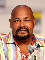 An African-American man with a bald head and a prominent goatee looking straight forward and sitting behind a microphone