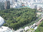 Bird eye view of a wooded park surrounded by tall buildings and adjacent to a rail line.