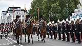 Soldiers in elaborate uniforms on horseback parading