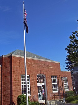 Three-quarter angle view of post office, a small brick building with hipped roof and a flagpole in front