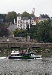 Un bateau sur la Loire, au second plan, sur une colline, un bâtiment blanc longé par un escalier.