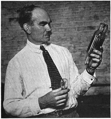 "De Forest, some time between 1914 and 1922, with two of his Audions, a small 1 watt receiving tube (left), and a later 250-watt transmitting power tube (right), which he called an ""oscillion"". Lee De Forest with Audion tubes.jpg"