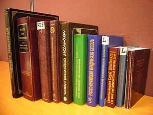 A stack of legal dictionaries on a desk.