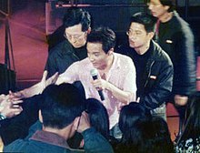 Cheung in a white shirt performing, surrounded by bodyguards
