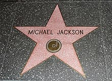 "A pink star with a gold color rim and the writing ""Michael Jackson"" in the center of the star. The star is indented into the ground and is surrounded by a marble color floor."