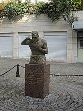 Statue avec un buste et un portrait, sur un socle sur lequel est célébré Marcel Cerdan, son palmarès et ses titres.