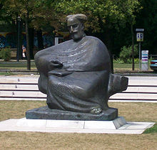 Gray statue in park of Bearded man in a robe, sitting