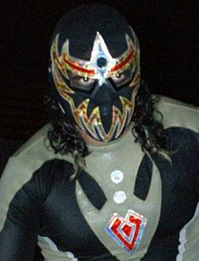 Máscara Dorada, wearing his trademark black and gold mask that covers his entire face except his eyes.