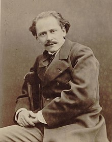 Middle-aged man, receding hair, neatly moustached, looking at camera