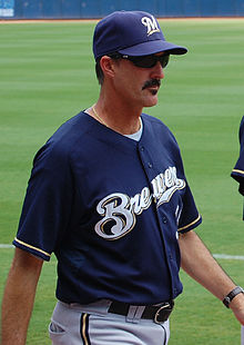 A thin, mustachioed man wearing a navy blue baseball cap and jersey