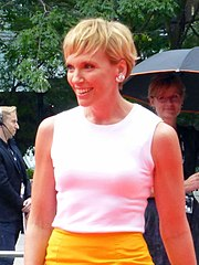 The 42-year-old is shown in a half-body shot. She wears a white top above a yellow skirt. She is smiling and facing to her left with her hair short, fair to light brown. Behing her to our left is a man wearing headphones and a microphone, while at the right is a woman holding an umbrella.