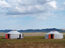 Two yurts, with people outside for scale