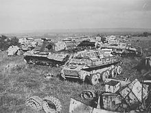 Wrecked vehicles are strewn across a field.