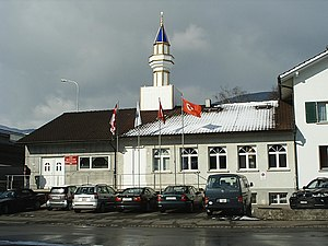 Religion in Switzerland - Minaret at the mosque of the local Turkish cultural association in Wangen bei Olten. Inaugurated in July 2009, after four years of legal and political controversy, this minaret, a Turkey-made plastic construction placed on the roof of the Turkish cultural center, was the initial motivation for the popular initiative voted upon later in 2009 which led to a nationwide ban of further minarets.