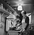 Mrs M Hasler cooks breakfast for her invalid husband in their home in Barnes, Surrey, during 1942. D9366.jpg