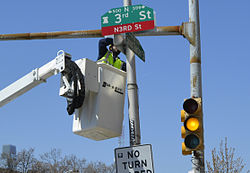 "City worker installing a ""N3RD St"" sign at the intersection with Spring Garden Street"