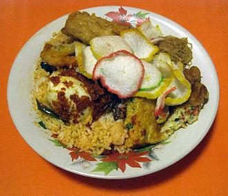 Nasi uduk - Traditional Betawi nasi uduk, mixing all the side dishes upon the nasi uduk plate, such as egg, tempeh, sambal, bihun goreng and krupuk