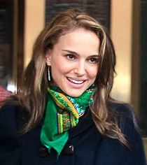 An image of a smiling woman with light brown hair in her 20s. She is wearing a tucked in green scarf with a dark colored coat.
