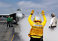 Navy Petty Officer 3rd Class Angela Crabtree directs the pilot of an F-A-18E Hornet to the steam catapult on the aircraft carrier USS Ronald Reagan (CVN 76) as the ship conducts flight operations 130504-N-AV746-037.jpg