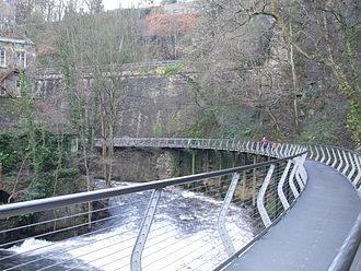 New Mills - The Millennium Walkway showing the part cantilevered from the railway embankment, and the part supported by pillars set in the river bed.