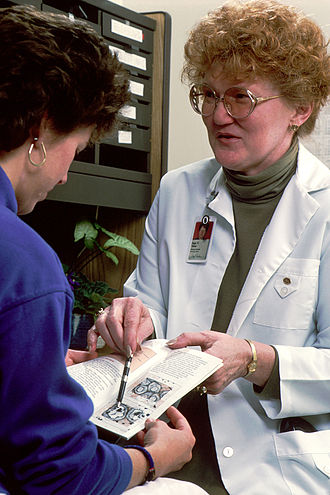 Nurse–client relationship - Nurse explaining information in a brochure with a client. Picture was taken by Bill Branson (Photographer).