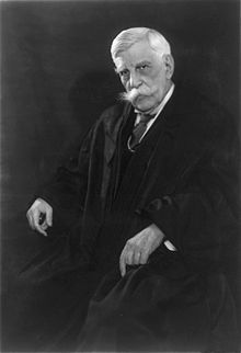 Man in shirt and tie and judge's robes seated in a chair