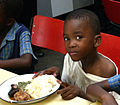 Orphan boy eating in Dzivarasekwa, Harare.jpg