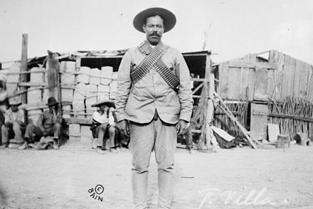 Villa wearing bandoliers in front of an insurgent camp. Undated photo. Pancho Villa bandolier.jpg