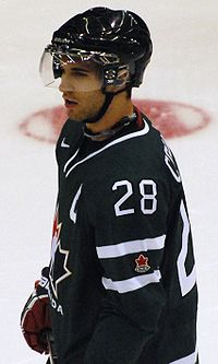 Hockey player in black uniform, with the number 28 on his shoulder. He stands on the ice, facing to the left of the camera.