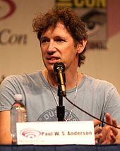 Paul W. S. Anderson, a Caucasian man in his mid-forties with messy brown hair seated in front of a microphone and looking to the side