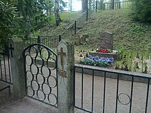 A modest tombstone, with flowers in front of it and an iron fence surrounding it is the gravesite for Red soldiers and civilians in Helsinki.