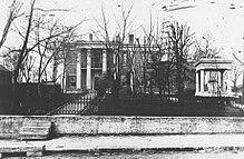 Duża posiadłość.  Zadaszony grób Polka znajduje się po prawej stronie, w pobliżu ulicy