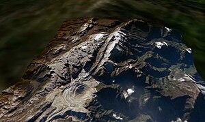 Satelliittikuva Puncak Jayasta (vuoden 2005 puolivälissä), kuparikaivoksesta vasemmassa etuosassa ja jäätikön jäännöksistä oikeassa yläkulmassa.  Huippukoko on keskimmäisen kylkiluun uloimman pisteen yläosassa.