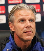 A middle-aged man of Nordic appearance photographed at a sporting press conference. His greying blond hair is brushed back, stubble is clearly visible on his face, and his dark blue eyes look up and to the viewer's right.