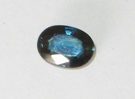 Dark blue sapphire, probably of Australian origin, showing the brilliant surface luster typical of faceted corundum gemstones. Sapphire III cropped flash.jpg