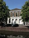 foto van Herenhuis met lijstgevel, rijk van stucwerk voorzien. In pleister gebosseerde parterre, waarin getoogde vensters. De vensters van de verdieping hebben hoofdgestellen. Kroonlijst met verdiepte velden en consoles