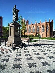 Schinkel-Standbild auf dem rekonstruierten Schinkelplatz in Berlin, im Hintergrund die von Schinkel entworfene Friedrichswerdersche Kirche (Quelle: Wikimedia)