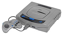 A Japanese Sega Saturn console. It is a gray system that resembles a DVD player. Attached is a gray controller with a dark gray D-pad on the left side and six buttons (three bigger black ones labeled A, B, and C, and three smaller blue ones labeled X, Y, and Z).