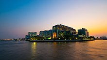 "A large complex of buildings, most over ten storeys high, on the bank of a river; one bears a sign with the words ""SIRIRAJ HOSPITAL""; another says ""FACULTY OF NURSING"""