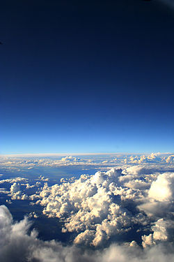 When seen from altitude, as here from an airplane, the sky's color varies from pale to dark at elevations approaching the zenith