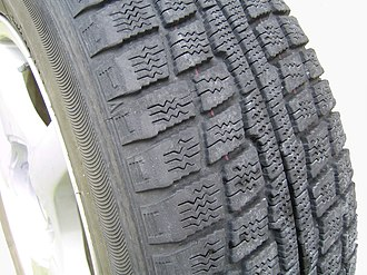 Snow tire - Winter tire, showing tread pattern designed to compact snow in the gaps.